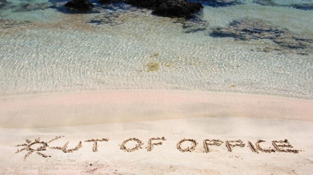OUT OF OFFICE written on sand on a beautiful beach, blue waves i
